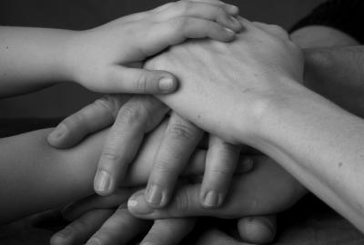 Hände, die aufeinander liegen und so den Zusammenhalt vieler symbolisieren
